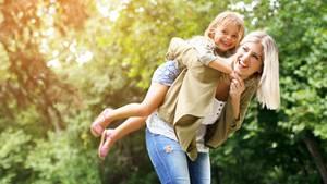 Eine Mutter trägt ein Mädchen huckepack