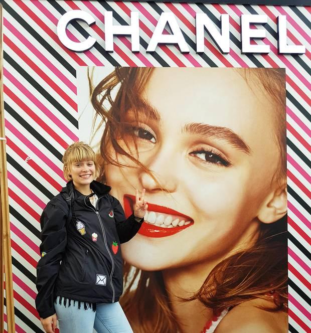 Mädchen in Regenjacke macht Peace-Zeichen vor Chanel-Plakat