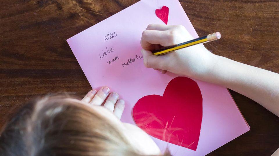 Ein Mädchen malt eine Karte zum Muttertag