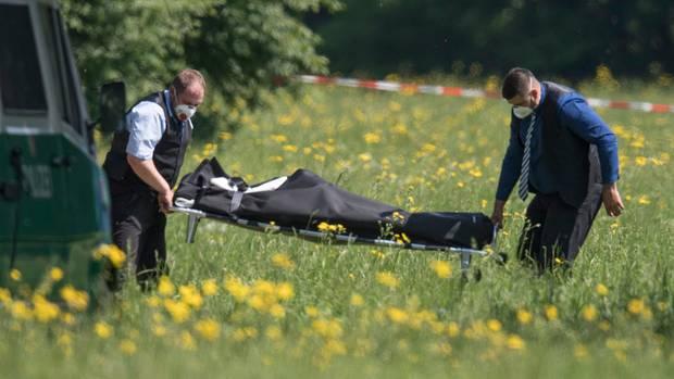 Mitarbeiter eines Bestattungsinstituts transportieren die Leiche von Irina K. aus dem Frankfurter Niddapark ab