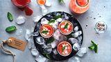 2 in 1: Deko und Vorspeise  Neben Blumen, Gestecken, Vasen, Lichtern und Kerzen können auch die Gänge eines Menüs den Tisch wunderbar schmücken. Für eine Sommerparty oder einen lauen Abend auf dem Balkon mit Freunden bieten sich zum Beispiel kleine Shot-Gläser oder Mini-Fläschchen (bis zu 100 ml) an, in denen selbstgemachte Gazpacho oder eine kalte Gemüsesuppe zum Trinken serviert werden. Sie dürfen wahlweise direkt am Platz neben den Tischkärtchen stehen oder bei lockeren Gartenfesten auch quer auf dem Tisch verteilt sein, sodass sich jeder etwas nehmen kann. Wer mag, bereitet gleich Suppen oder Drinks in zwei, drei verschiedenen Farben zu und serviert in unterschiedlich geformten Fläschchen und Schnaps-Gläsern: So passt der Welcome-Drink auch gleich noch zum Farb-Konzept des Abends!