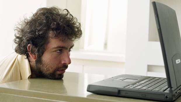 Ein Mann schaut resigniert auf seinen Laptop-Bildschirm