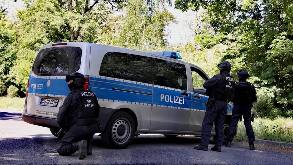 Drei Polizisten stehen mit Helmen und Sturmhauben auf an einem silber-blauen Transporter der Polizei