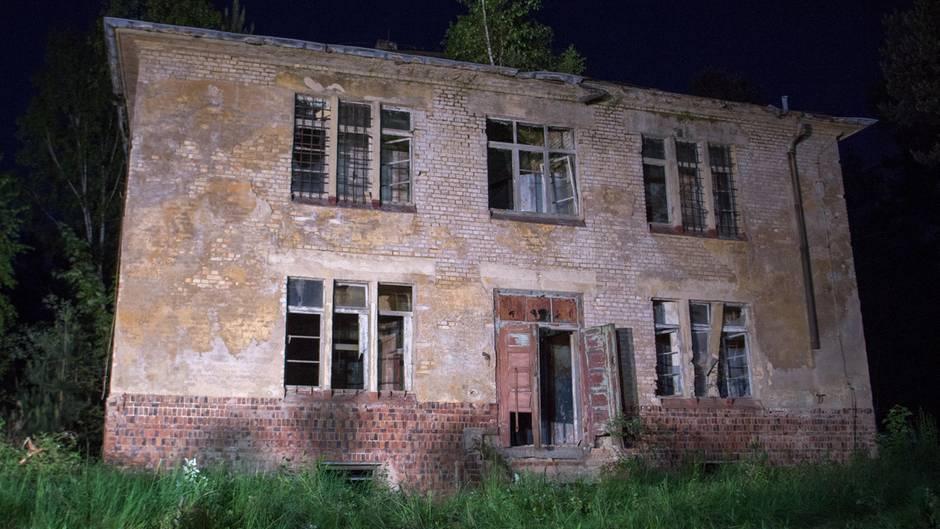 Scheinwerfer strahlen das Haus in Königsbrück, Sachsen, an, in dem sich der gesuchte mutmaßliche Mörder verschanzt hatte