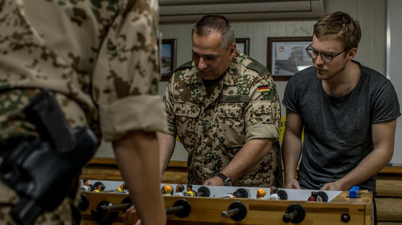 Soldaten und der Reporter spielen Tischfußball