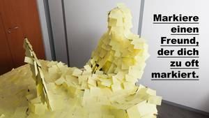 Ein Mann sitzt an einem Schreibtisch voll geklebt mit Post-Its