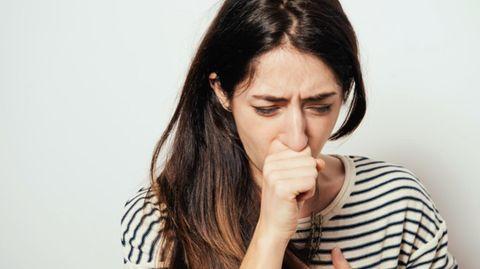 Frau hustet und hält sich die Hand vor den Mund