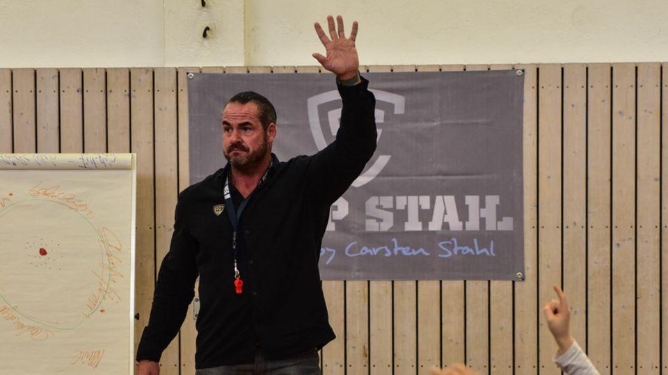 Carsten Stahl mit erhobenem Arm vor einer Gruppe Schüler, die auch den Arm heben