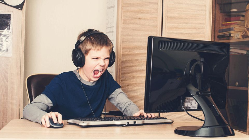 Eine Junge sitzt mit Kopfhören am Computer