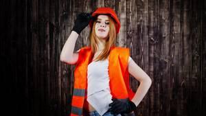 Rothaarige Frau in bauchfreiem Top, Hotpants, orangener Warnweste und Schutzhelm
