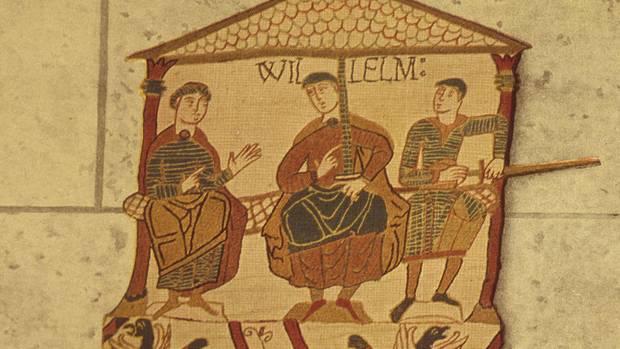 """Ein Bild auf dem Teppich von Bayeux zeigt drei sitzende Männer in einem Haus. Über dem mittlerem steht """"Willelm"""" für Wilhelm"""