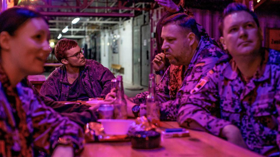 Bundeswehrsoldaten und Reporter Frederik Seeler sitzen an einem Tisch und trinken Bier