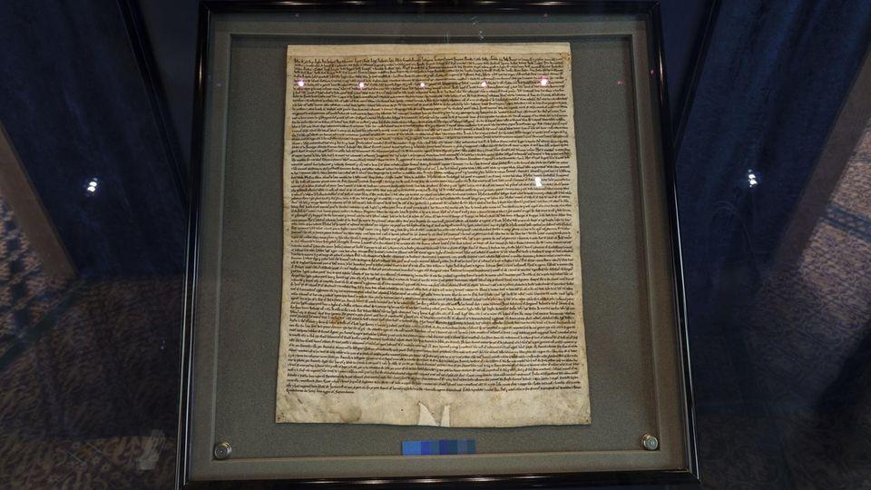 In einer dunkel gerahmten Vitrine liegt ein eng beschriebenes Stück Pergament: die Magna Carta