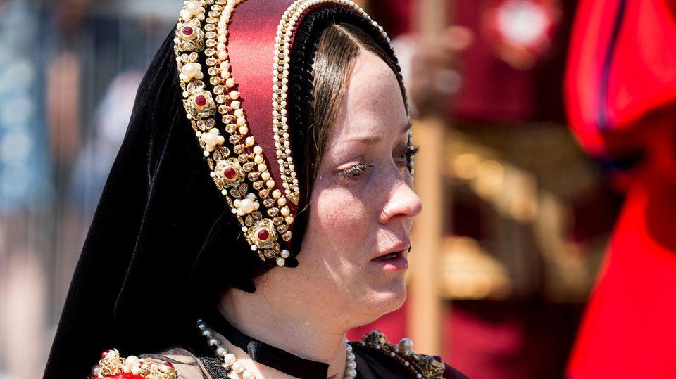 Eine dunkelhaarige Schauspielerin steht in einem dunkelroten, historischen Gewand mit einer passenden Haube in der Sonne