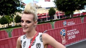 Eine Frau mit blonden, hochtoupierten Haaren lächelt vor einem Plakat mit dem Logo der Fußball-WM 2018 in Russland