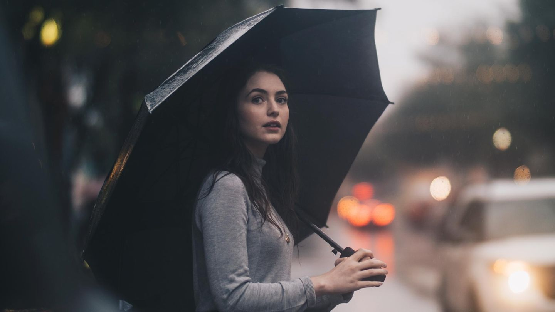 Frau mit Regenschirm auf Straße