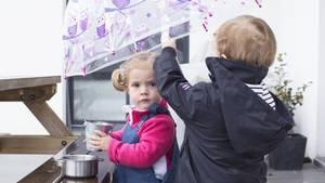 Zwei kleine Kinder spielen im Regen