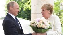 Wladimir Putin begrüßt Angela Merkel mit einem Blumenstrauß