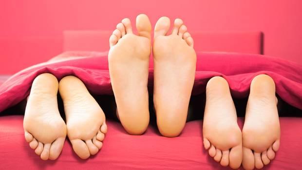 Sechs Füße in einem Bett