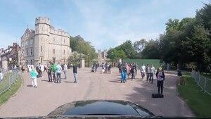 Vor der Einfahrt zu Schloss Windsor stehen Touristengruppen. Am unteren Bildrand ist die schwarze Motorhaube des Autos zu sehen