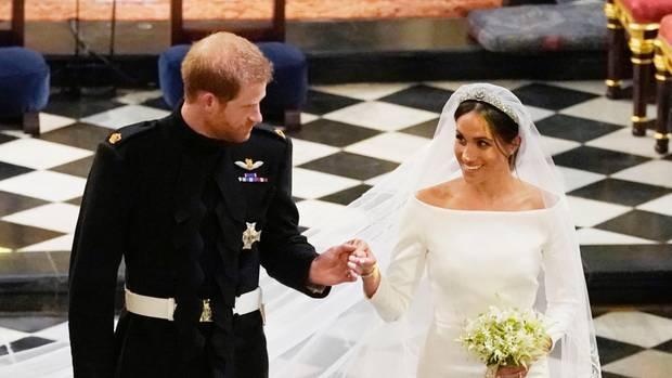 Hand in Hand schreiten Prinz Harry und Meghan Markle als Ehepaar durch die Kirche in Windsor. Sie lächelt ihn an.