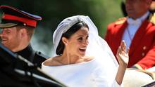 Meghan Markle winkt im Brautkleid aus der offenen Kutsche den Zuschauern am Straßenrand, Prinz Harry sitzt in Uniform neben ihr