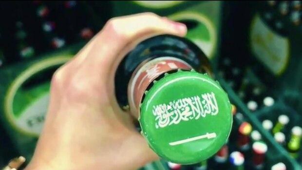 Auf einer Bierflasche ist ein Kronkorken mit dem islamischen Glaubensbekenntnis in weiß auf grünem Grund zu sehen