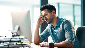 Genervter Mann vor Computer im Büro