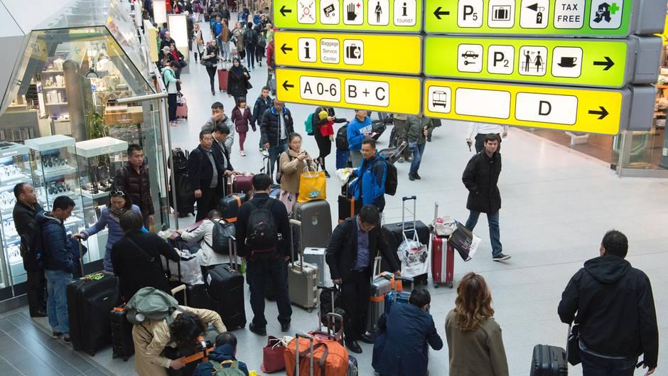 Mehrere Menschen warten an einem Flughafen mit ihren Koffern