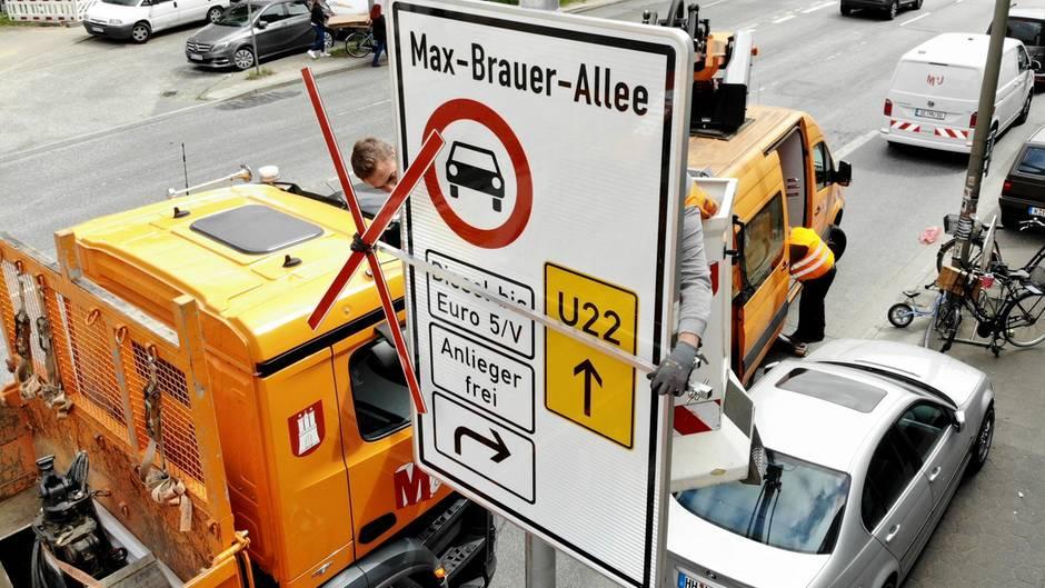 Handwerker bauen ein Schild auf, welches auf das Diesel-Fahrverbot in Hamburg verweist