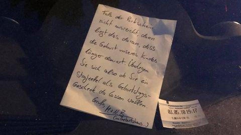 Ein handgeschriebener Brief liegt in der Windschutzscheibe eines Autos