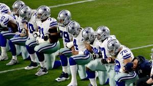 Spieler der Dallas Cowboys knien auf dem Rasen