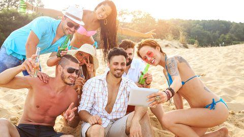 Feiernde Menschen am Strand machen ein Selfie