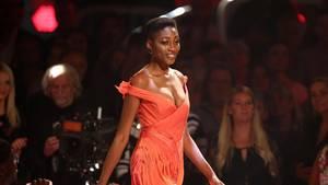 Ein farbiges Model läuft in einem schulterfreien, apricotfarbenen Kleid über einen Laufsteg im TV-Studio