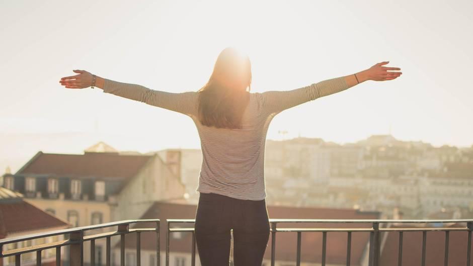 Eine Frau steht auf einem Balkon und breitet die Arme aus