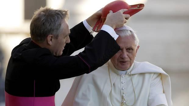 """Noch immer sorgt sich Gänswein als Sekretär um Papst emeritus Benedikt. Als der noch im Amt war, setzte sein """"Mitarbeiter"""" ihm auch mal einen roten Cappello Saturno über den weißen Zucchetto"""