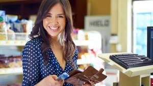 Eine Frau steht an einer Supermarktkasse und bezahlt