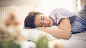 Eine Frau liegt in einem Bett und schläft