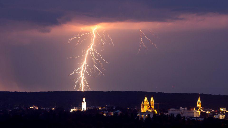 Blitze entladen sich während eines Gewitters hinter der Stadt Bad Homburg in Hessen