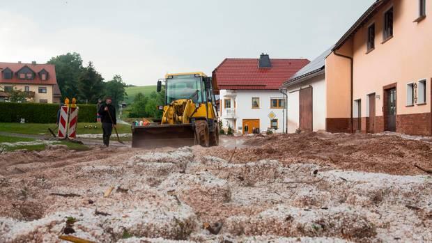 Hessen, Hetzerode: Nach Starkregen und Hagelschlag wird eine blockierte Straße geräumt