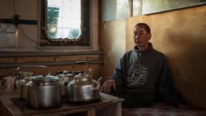 Ein Mann auf dem Fischerkahn auf der Wolga. Hier herrscht kein Luxus. Auf zwei Camping-Platten bereitet man für die gesamte Mannschaft das Essen zu. Das Klo ist im Schilf, das Bad auf der Reling. Umgerechnet 150 Euro im Monat verdienen die Fischer in der Gegend.