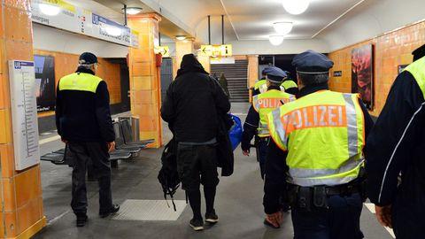 Mehrere Polizisten in Westen begleiten einen schwarz gekleideten Mann