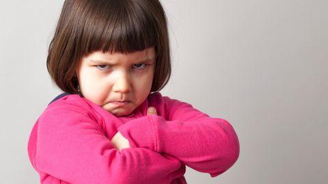 Ein wütendes Mädchen mit wütendem Gesucht und überkreuzten Armen