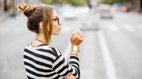 Eine junge Frau raucht auf der Straße eine Zigarette