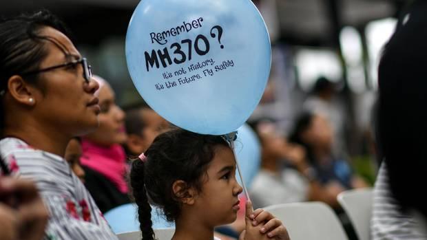 Mädchen hält Luftballon in Gedenken an verschollenen Flug MH370