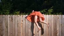 FOMO: Eine Frau hängt über einem Zaun, um auf die andere Seite zu schauen