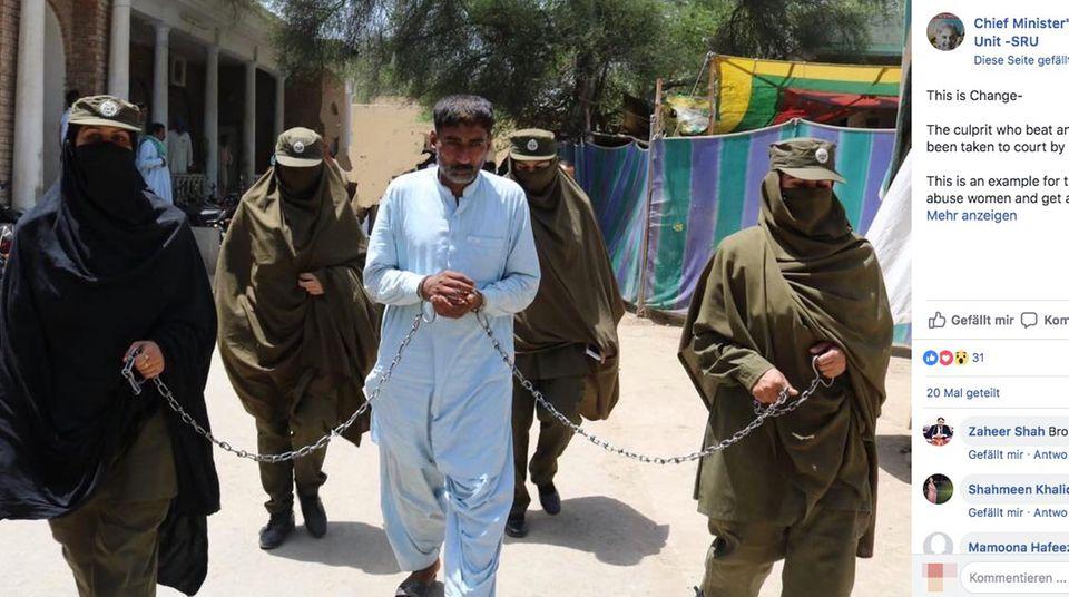 Ein weiß gekleideter Mann wird in Handschellen mit langen Ketten abgeführt