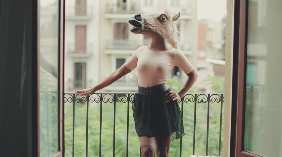 Eine Frau steht auf dem Balkon. Vielleicht ist ja gerade auf Wohnungssuche?