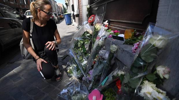 Eine Frau kauert an einer improvisierten Gedenkstätte für die Opfer des Attentäters von Lüttich