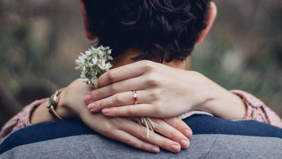 Hochzeit: Ein Pärchen umarmt sich, an der Hand der Frau sieht man einen Ring